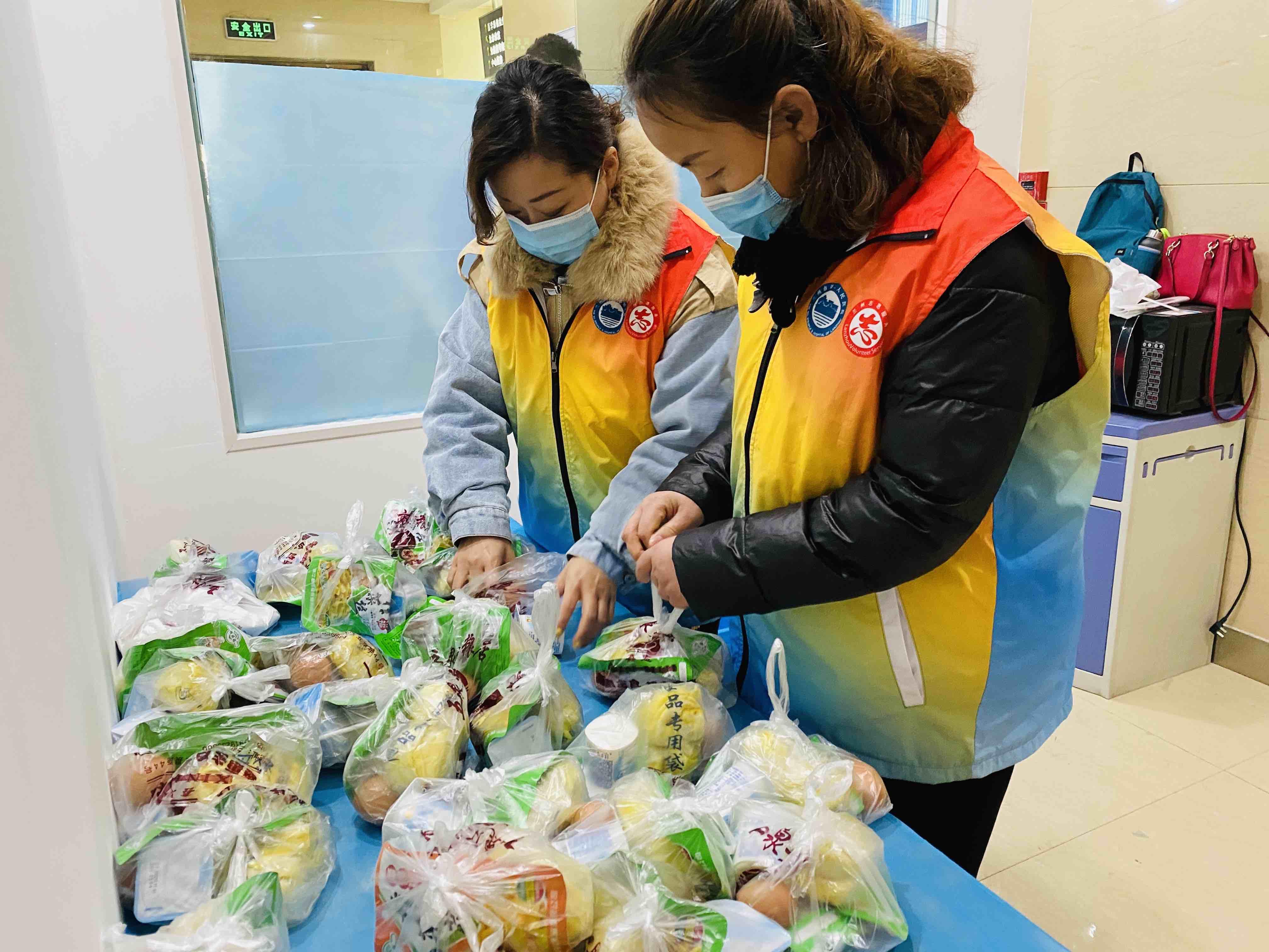 志愿者王艺蓉(左)分装早餐